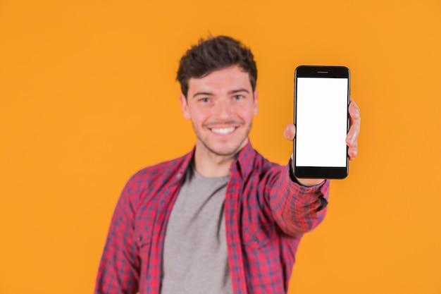 Porträt eines lächelnden jungen mannes, der leeren handy des weißen bildschirms zeigt Kostenlose Fotos
