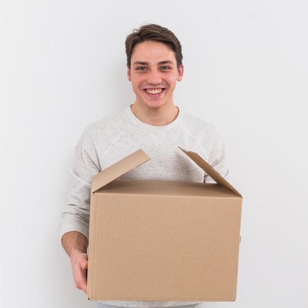 Porträt eines lächelnden jungen mannes, der pappschachtel gegen weißen hintergrund hält Kostenlose Fotos
