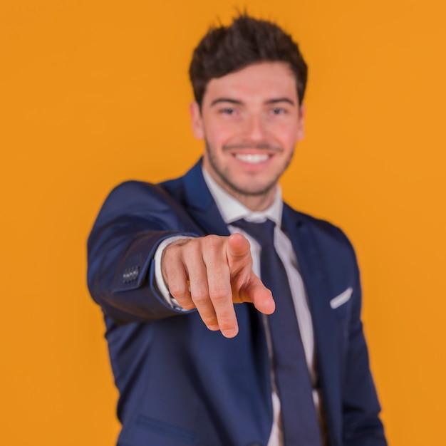 Porträt eines lächelnden jungen mannes, der seinen finger gegen einen orange hintergrund zeigt Kostenlose Fotos