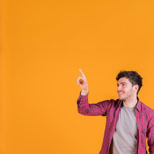 Porträt eines lächelnden jungen mannes, der seinen finger gegen orange hintergrund zeigt Kostenlose Fotos