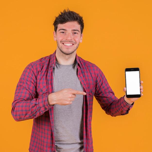 Porträt eines lächelnden jungen mannes, der seinen handy gegen einen orange hintergrund zeigt Kostenlose Fotos