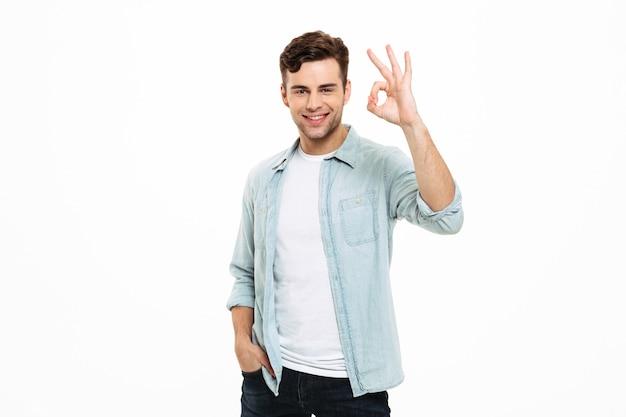 Porträt eines lächelnden jungen mannes, der steht und ok zeigt Kostenlose Fotos