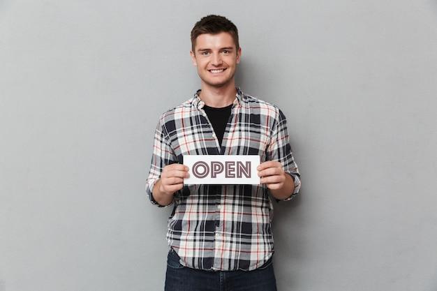Porträt eines lächelnden jungen mannes mit offenem zeichen Premium Fotos