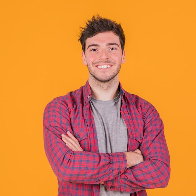 Porträt eines lächelnden jungen mannes mit seinem arm kreuzte stellung gegen einen orange hintergrund Kostenlose Fotos