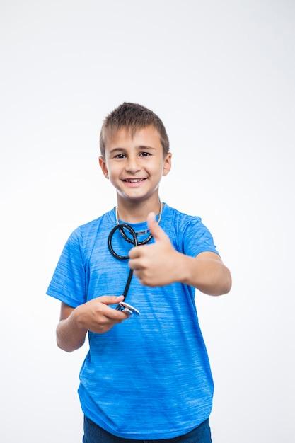 Porträt eines lächelnden jungen mit stethoskop daumen oben gestikulierend Kostenlose Fotos