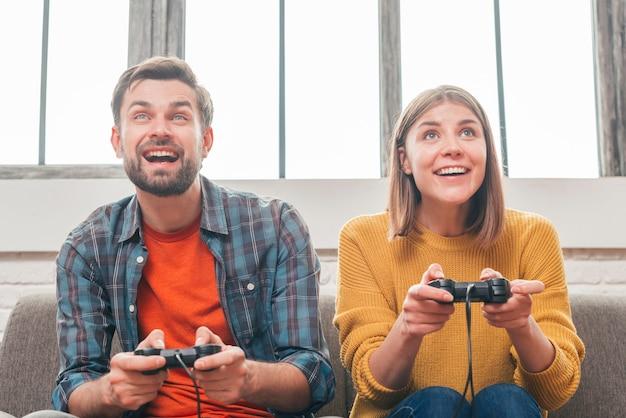 Porträt eines lächelnden jungen paares, welches das videospiel mit steuerknüppel spielt Kostenlose Fotos