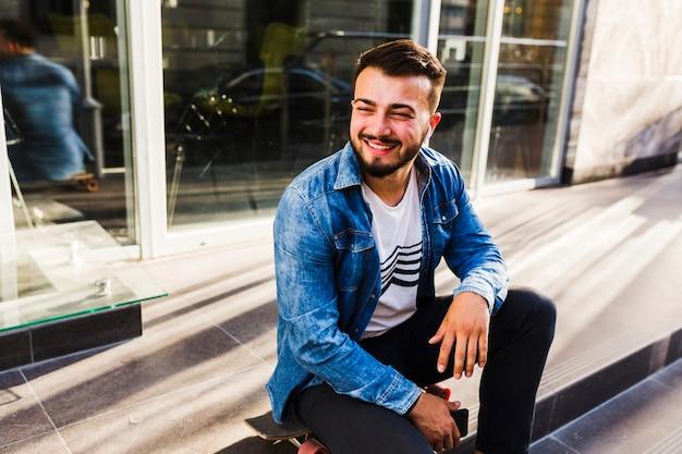 Porträt eines lächelnden jungen skateboardfahrers, der auf treppenhaus sitzt Kostenlose Fotos