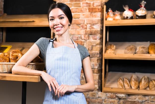 Porträt eines lächelnden jungen weiblichen bäckers, der kamera betrachtet Kostenlose Fotos