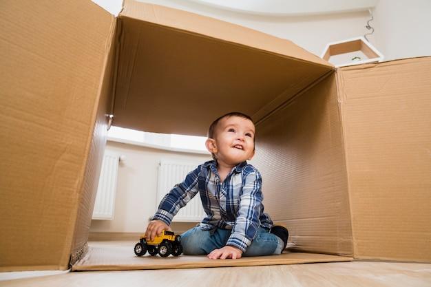 Porträt eines lächelnden kleinkindjungen, der mit spielzeugfahrzeugen spielt Kostenlose Fotos