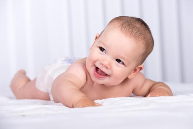 Porträt eines lächelnden kriechenden babys auf dem bett im raum. Premium Fotos