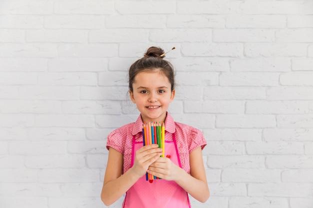 Porträt eines lächelnden mädchens, das in der hand gegen die weiße backsteinmauer farbige bleistifte hält Kostenlose Fotos