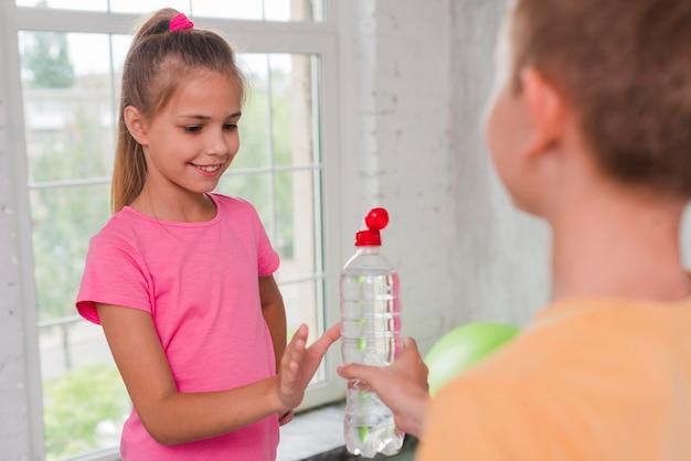 Porträt eines lächelnden mädchens, das wasserflasche von ihrem freund empfängt Kostenlose Fotos