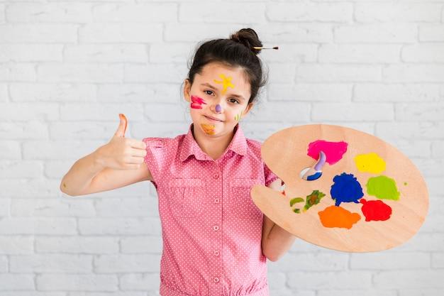 Porträt eines lächelnden mädchens, welches die multi farbige palette zeigt daumen herauf das zeichen steht gegen weiße backsteinmauer hält Kostenlose Fotos