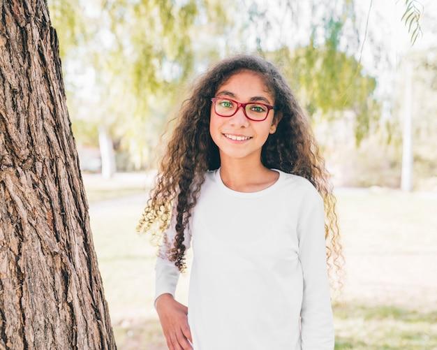 Porträt eines lächelnden mädchens, welches die roten gläser betrachten kamera trägt Kostenlose Fotos