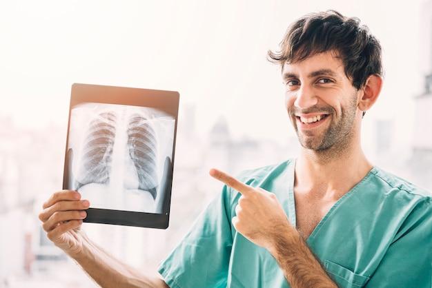 Porträt eines lächelnden männlichen doktors, der kastenröntgenstrahl zeigt Kostenlose Fotos