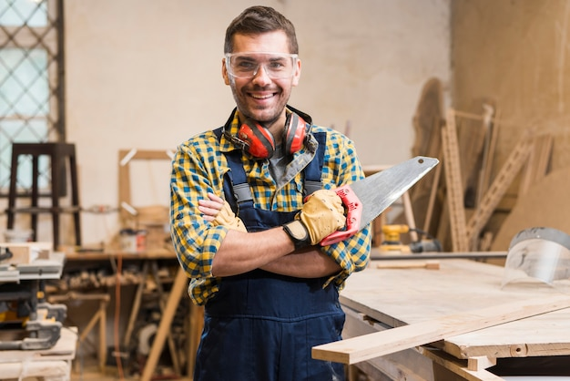 Porträt eines lächelnden männlichen tischlerholding handsaw, der kamera betrachtet Kostenlose Fotos
