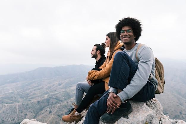 Porträt eines lächelnden mannes, der auf die oberseite des felsens genießt mit seinem freund sitzt Kostenlose Fotos