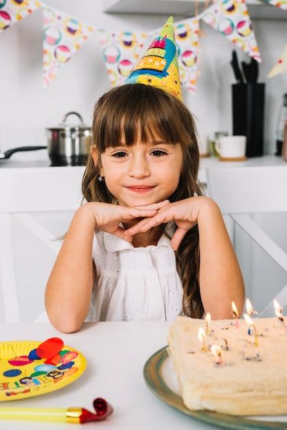 Porträt eines lächelnden netten geburtstagsmädchens mit partyhut auf ihrem kopf Kostenlose Fotos