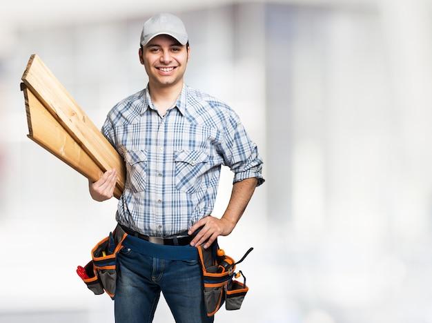 Porträt eines lächelnden tischlers, der hölzerne planken hält. heller hintergrund Premium Fotos
