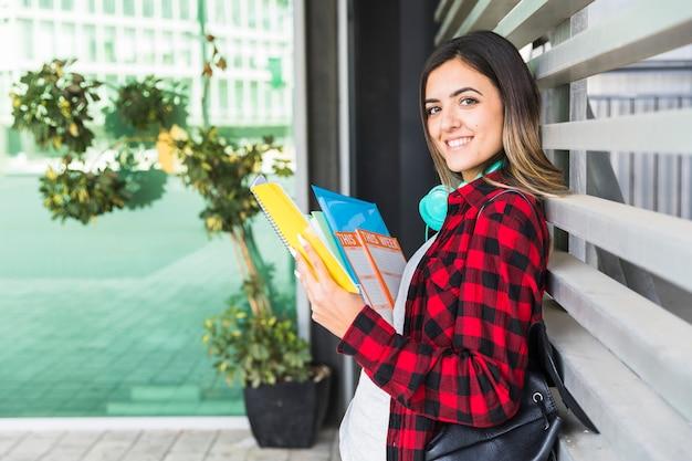 Porträt eines lächelnden weiblichen hochschulstudenten, der in der hand die bücher sich lehnt an der wand hält Kostenlose Fotos