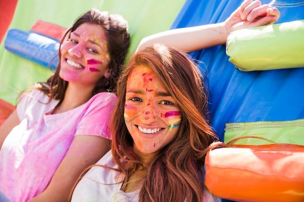 Porträt eines lächelns zwei junge frauen mit holi farbgesicht Kostenlose Fotos