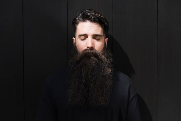 Porträt eines langen bärtigen jungen mannes mit auge schloss vor schwarzer backsteinmauer Kostenlose Fotos