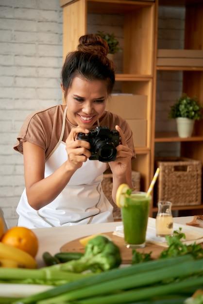 Porträt eines lebensmittelbloggers, der foto des smoothie macht Kostenlose Fotos