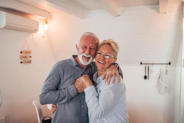 Porträt eines liebevollen älteren paares zuhause. umarmen, lächeln und blick in die kamera. Premium Fotos