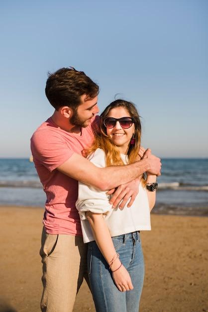 Porträt eines liebevollen jungen paares, das am strand gegen blauen himmel steht Kostenlose Fotos