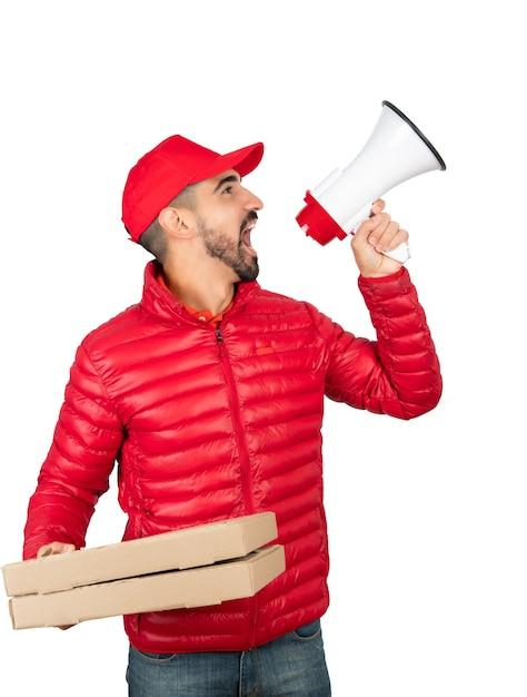 Porträt eines lieferers in roter arbeitskleidung und im megaphon vor weißem hintergrund schreiend Premium Fotos