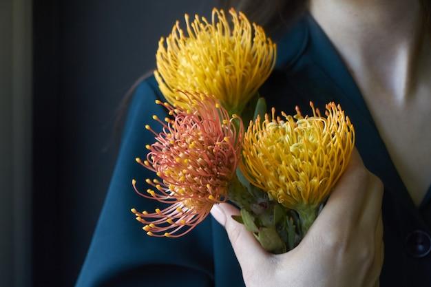 Porträt eines mädchens, das drei gelbe und orange proteas hält Premium Fotos