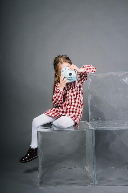 Porträt eines mädchens, das durch die sofortige kamera sitzt auf transparenten würfeln gegen grauen hintergrund fotografiert Kostenlose Fotos