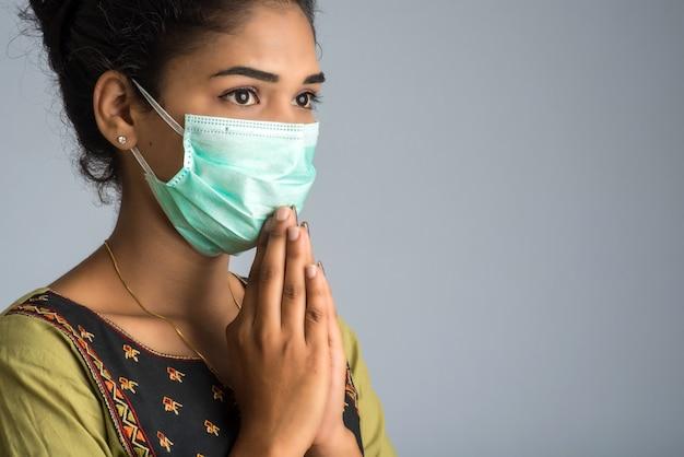 Porträt eines mädchens, das eine medizinische maske trägt, die gruß mit namaste-geste tut. Premium Fotos