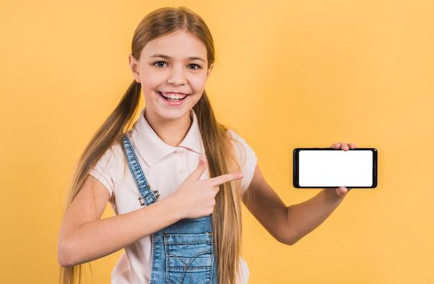 Porträt eines mädchens, das ihren finger am intelligenten telefon zeigt die weiße bildschirmanzeige steht gegen gelben hintergrund zeigt Kostenlose Fotos