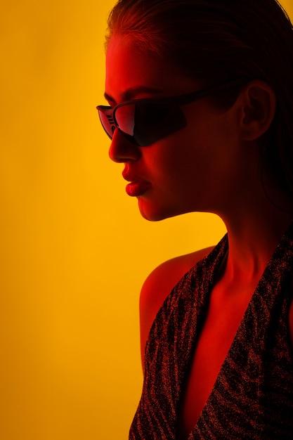 Porträt eines mädchens in der sonnenbrille mit einer roten leuchte Premium Fotos