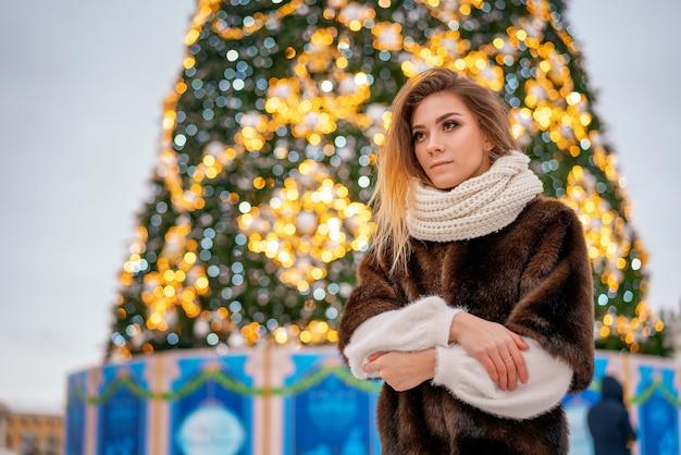 Porträt eines mädchens in einem pelzmantel auf dem hintergrund eines weihnachtsbaums. Premium Fotos