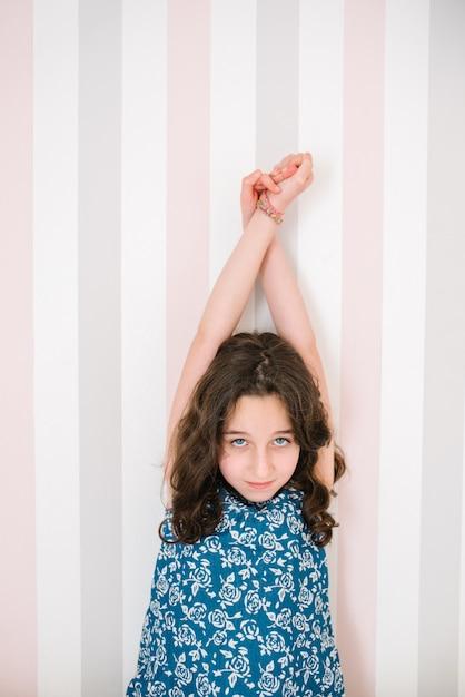 Porträt eines mädchens mit langen braunen haaren und blauen augen mit ausgestreckten armen vor einem gestreiften hintergrund Premium Fotos