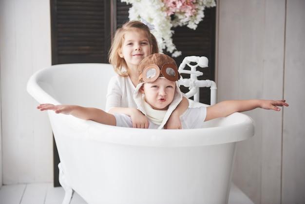 Porträt eines mädchens und eines jungen im versuchshut, der im badezimmer an den piloten oder an den seeleuten spielt. reisen, kindheit und die verwirklichung von träumen Premium Fotos