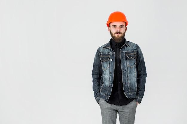 Porträt eines männlichen architekten tragenden hardhat, der gegen weißen hintergrund steht Kostenlose Fotos