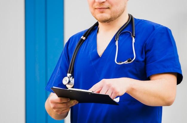 Porträt eines männlichen doktors mit stethoskop um seinen hals den medizinischen bericht überprüfend Kostenlose Fotos