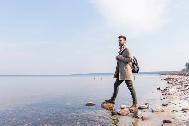Porträt eines männlichen reisenden, der nahe dem see mit seinem rucksack steht Kostenlose Fotos