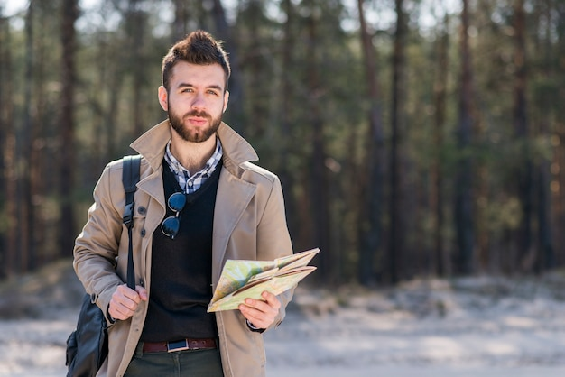 Porträt eines männlichen reisenden mit seinem rucksack auf der schulter, welche in der hand die karte betrachtet kamera hält Kostenlose Fotos