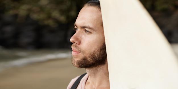 Porträt eines männlichen surfers, der sich bereit macht, riesige mächtige wellen zu erobern Kostenlose Fotos