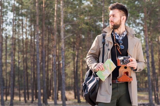 Porträt eines männlichen wanderers mit der kamera und karte, die im wald stehen Kostenlose Fotos