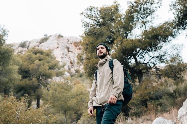 Porträt eines männlichen wanderers mit seinem rucksack, der in den bergen wandert Kostenlose Fotos