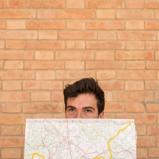 Porträt eines mannbedeckungsgesichtes mit einer karte Kostenlose Fotos