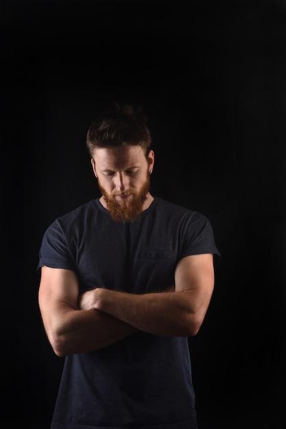 Porträt eines mannes blick nach unten und mit verschränkten armen und schwarz Premium Fotos