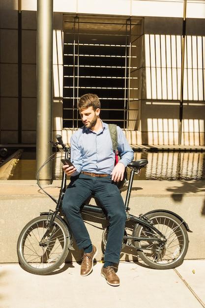 Porträt eines mannes, der den handy sitzt mit fahrrad verwendet Kostenlose Fotos