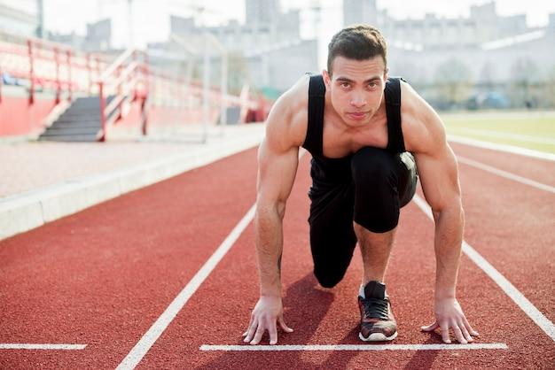 Porträt eines mannes, der die position für das laufen auf der athletischen bahn einnimmt Kostenlose Fotos
