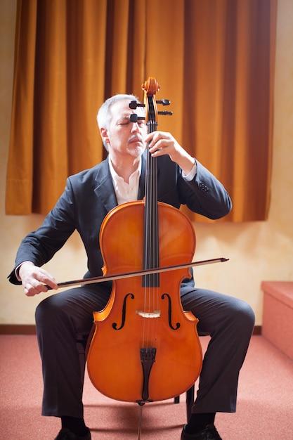 Porträt eines mannes, der ein cello spielt Premium Fotos